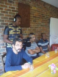 Caméraman debout près de trois participants assis autour d'une table