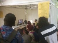 Sous une grande tente, groupe de personnes assises à regarder une vidéo